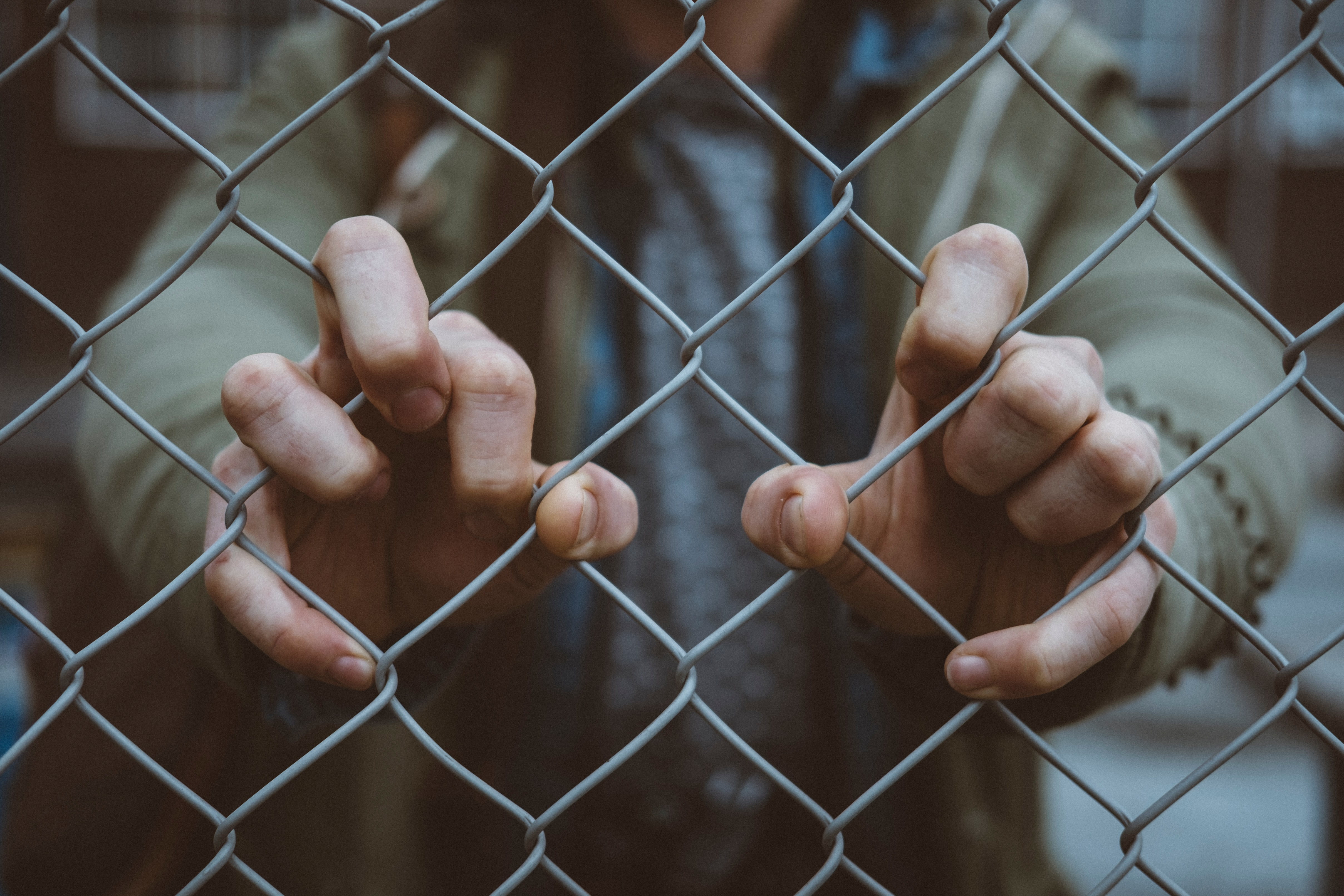Photo: Hands holding a fence